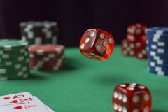 Red dice, casino chips, cards on green felt stock photography