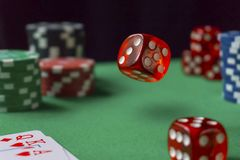 Red dice, casino chips, cards on green felt stock photo