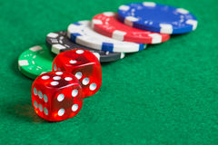 Red dice on a casino table with chips Stock Photography