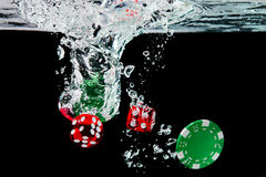 Red dice and chips in the water on black background royalty free stock photos