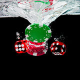 Red dice and chips in the water on black background royalty free stock photography