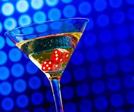 Red dice in the cocktail glass on blue bokeh Stock Image