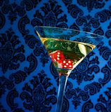 Red dice in the cocktail glass on blue vintage victorian damask. Background royalty free stock photography