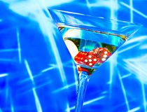 Red dice in the cocktail glass on blur blue Royalty Free Stock Photos