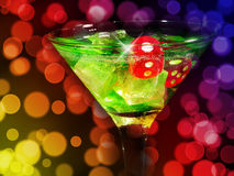 Red dice in a cocktail glass on bokeh background. casino series.  royalty free stock photo