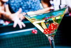 Red dice in the cocktail glass in front of gambling table Royalty Free Stock Image