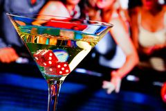 Red dice in the cocktail glass in front of gambling table Stock Images