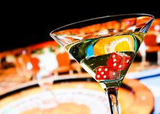 Red dice in the cocktail glass in front of roulette wheel Stock Image