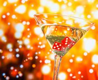 Red dice in the cocktail glass on golden bokeh stock images