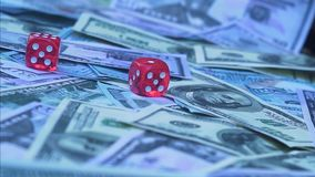 Red dice falling on money. Gambler playing game at casino stock video footage