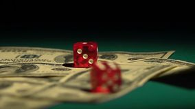 Red dice falling on money, gambler playing game at casino, addiction to gambling. Stock footage stock footage