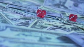 Red dice falling on money. Gambler playing game at casino slowmotion stock video footage