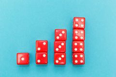 Red dice in the form of a graph, rising from one to four, on a blue background stock images