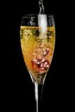 Red dice in the glass of champagne being filled with a lot of bubbles Royalty Free Stock Photos