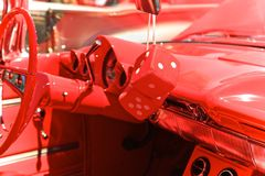 Red dice. Large red dice hanging from inside rear view mirror of an old red royalty free stock photography