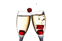 Red dice in movement in two flutes with gold bubbles Stock Photos