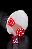 Red dice on old wood black table near a container Royalty Free Stock Photo