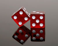 Red Dice Reflecting. Pair of red dice reflecting on black surface stock photography