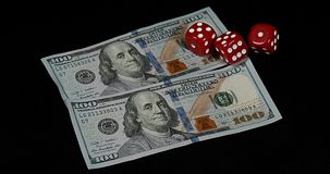 Red Dice rolling on Dollar Bills against Black Background, stock footage
