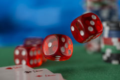 Red dice rotates in the air, casino chips, cards on green felt Royalty Free Stock Images