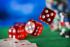 Red dice rotates in the air, casino chips, cards on green felt Stock Photography