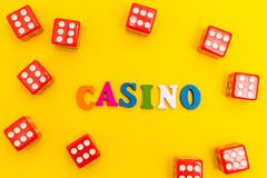 Red dice with sixes on a yellow background, casino inscription.  stock photo