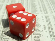 Red dice on stock report. Red dice showing seven on stock market section of newspaper. focus on leading top corner of front dice. very shallow depth of field royalty free stock photo