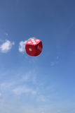 Red dice suspended in the SKY. Red dice thrown up into the sky stock photos