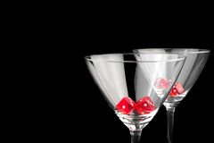 Red dice in two cocktail glasses. On black background with space for text Stock Images