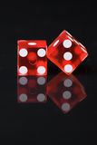 Red Dice with White Pips on Reflective Black Table. Red dice showing white dots four and three toward viewer and almost showing snake eyes or 1 and 5 upward Stock Photography