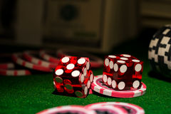 Red dices on chip and dollar bills, casino concept Royalty Free Stock Image