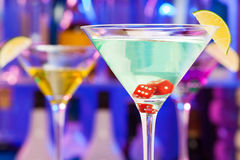 Red dices in cocktail glasses with bar on back Royalty Free Stock Images