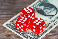 Red dices with one dollar banknote on wooden table royalty free stock image