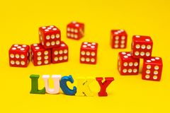 Red dices, sixes, on a yellow background, the inscription stock images