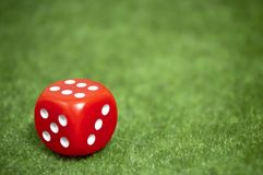 Red Die. Casino Red die over a green carpet Stock Photography