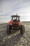 Red diesel beach tractor. A red tractor covered in red fender shipping buoys stands on the beach Stock Image
