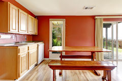 Red dining room with rustic table and bench Royalty Free Stock Photography