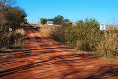 The Red Dirt of Oklahoma. The dirt farm road at Enid Oklahoma, red dirt, little creek cross/bridge, weight limit 13 tons sign Stock Image