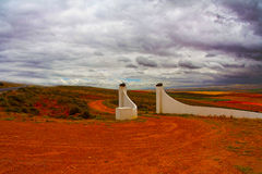 Red Dirt Road Through Gates in Countryside. Red Dirt Road Leading Through White Stone Gates in Isolated South African Countryside with Dark Storm Clouds Overhead Stock Photos