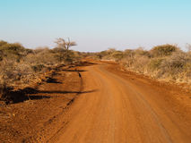 Red dirt track winds through African landscape Stock Image