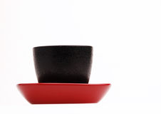 In the Red Dish (3). Black cup in a red dish Stock Photo