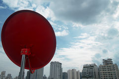 Red satellite with cloud. Red dish on the top of the building with cloud, some time it make you to think about something stock images