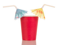 Red disposable cup with straw umbrellas isolated on white. Royalty Free Stock Photography