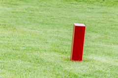 The red distance marker pole to inform range of golfing with blu Royalty Free Stock Photos