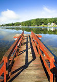 Red dock, beautiful lake. Vertical perspective. Beautiful reflection and early morning light stock image