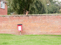 A red dog poo box bin outside against wall no people royalty free stock photography