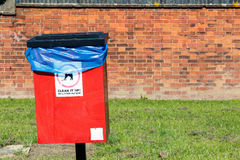 Red Dog Waste Bin. Against a brick wall Stock Image