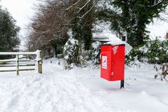 Red dog-waste bin covered in snow. With trees in the background Stock Photography