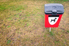 Red dog waste bin on green lawn in park area. Plastic garbage bin for pets dung with black and white dog symbol on it. Bright red box for animals waste on green Royalty Free Stock Photo