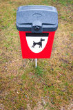 Red dog waste bin on green lawn in park area. Plastic garbage bin for pets dung with black and white dog symbol on it. Bright red box for animals waste on green Royalty Free Stock Images
